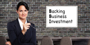 Lady Holding her Glasses. Whiteboard in the Background that says Backing Business Investment