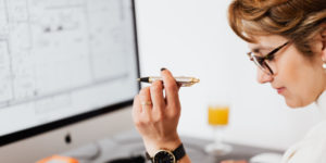 Lady Holding a Pen and Sitting at her Desk